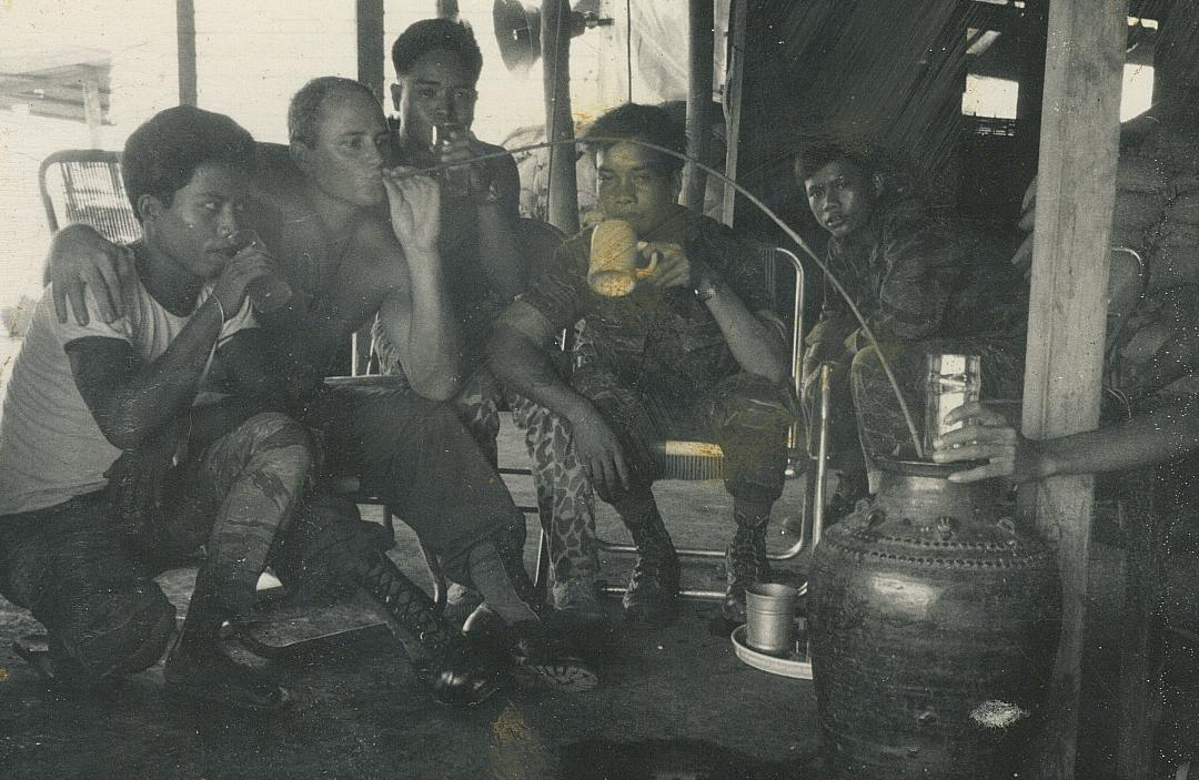 SSG Lonny Holmes drinking rice wine with the \'Montagnards, Plei Djereng, A-251 July 68. It gives you a very bad hangover.