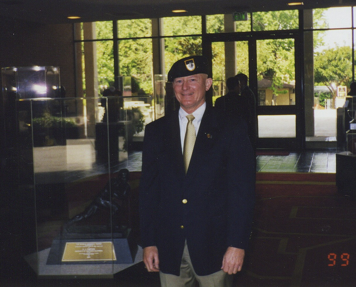 Lonny Holmes Wearing LTC Wm Taylors Beret Standing Adjacent to Heisman Trophy of O.J. Simpson in USC\'s Heritage Hall