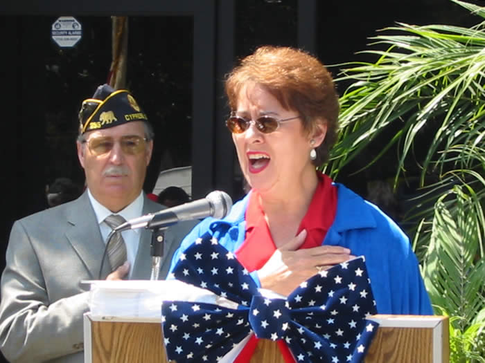 Post Secretary Bonny Jacobs sings the National Anthem