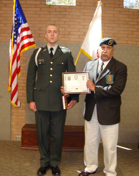 "Terry Cagnolatti presenting Special Forces Certificate and Medal of Merit and a copy of  'Tilt'  Striker Meyers book, ""On the Ground"" to  USC Cadet David Shipko."