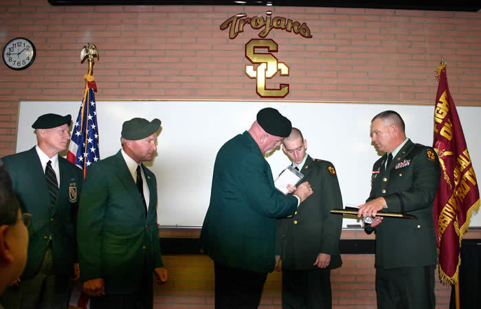 University of Southern California Trojan Battalion LTC Robert F. Huntly, Commanding, to right. Jim Duffy pinning Special Forces Medal of Merit on USC ROTC Cadet Mark Thomas. Lonny Holmes and Len Fein on left.